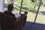 Lady reading a book in a chair for Australian Reading Hour 20.09.2018.PNG