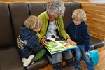 Grandmother reading with two young children