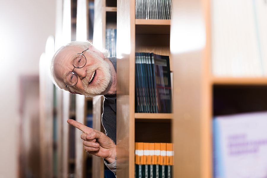 Older man poking his head out of library shelving